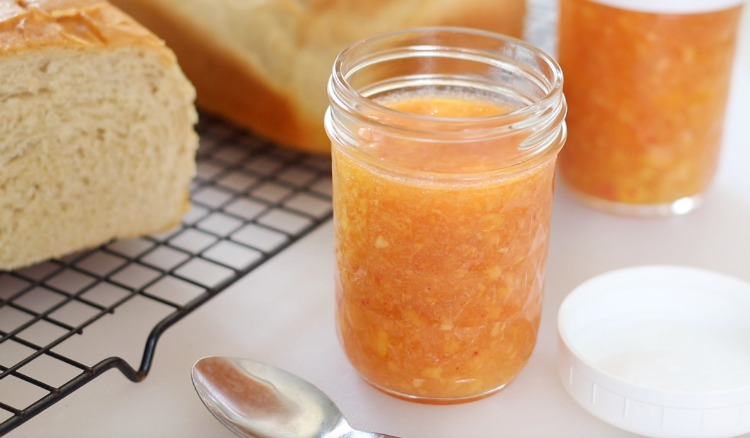 open jar of peach freezer jam next to a loaf of bread