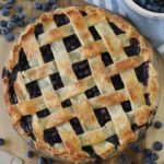 lattice top blueberry pie baked and resting on cutting board