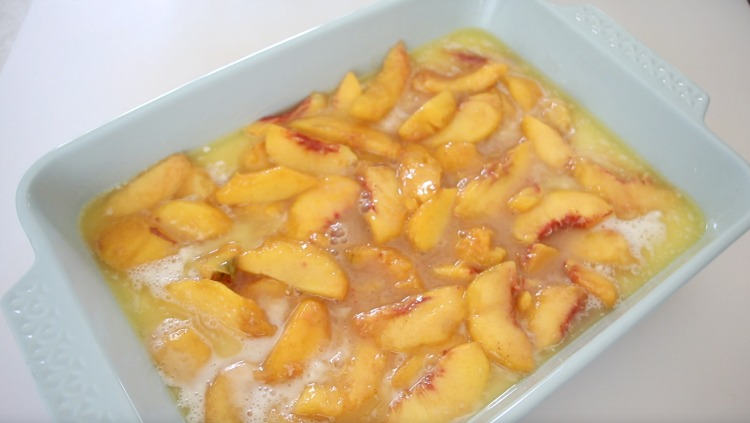 peaches poured over butter and batter in baking dish
