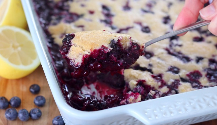 serving spoon with scoop of blueberry lemon cobbler