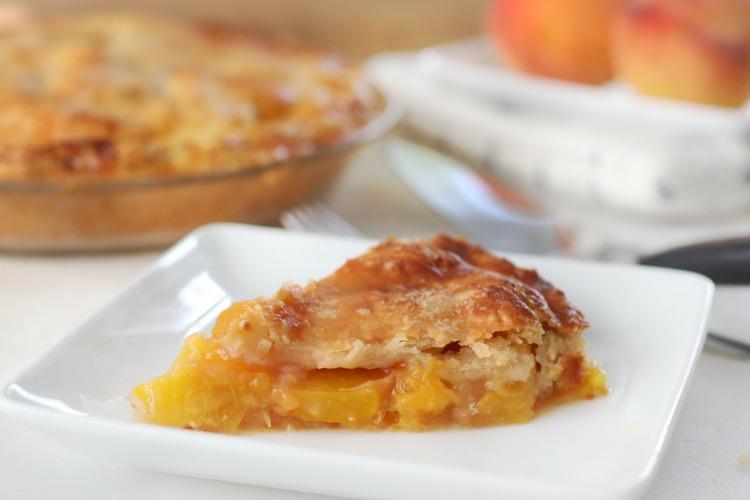 slice of warm peach pie on white plate