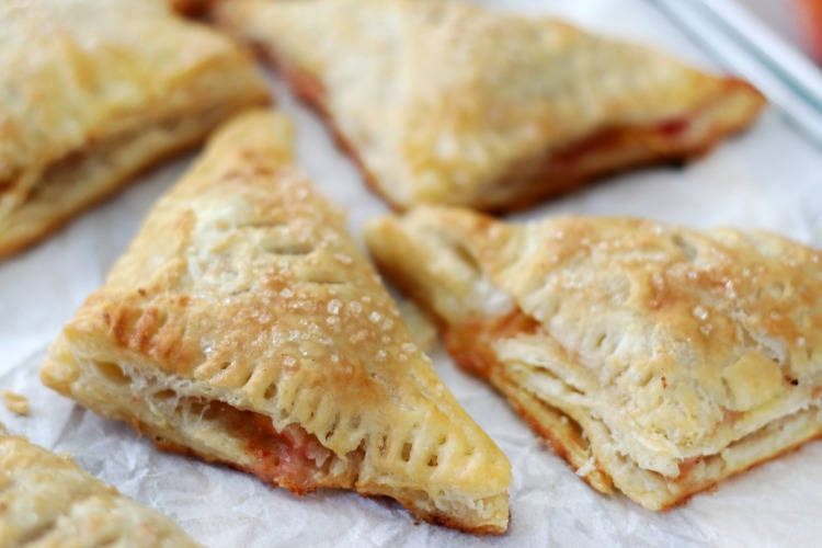 baked peach turnovers on parchment paper