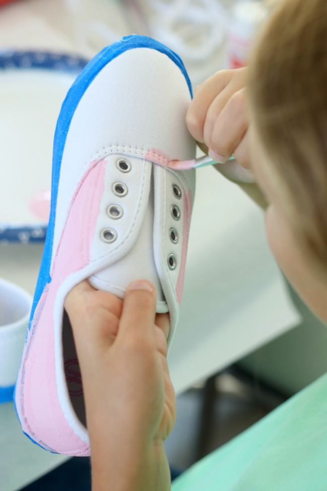 child painting shoes with acrylic paint