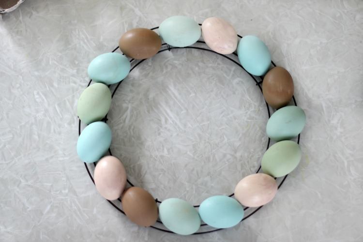 wire wreath base with painted wooden eggs