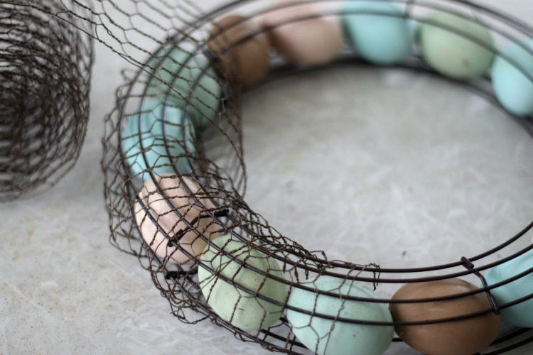 wooden eggs on wreath frame being wrapped in chicken wire