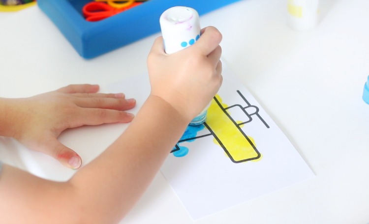 child coloring airplane page with dot markers