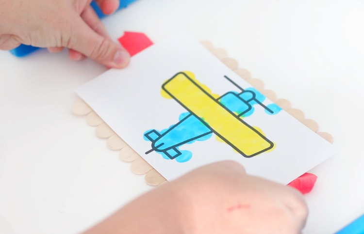 gluing coloring page to popsicle sticks