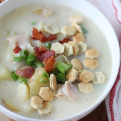 bowl of clam chowder with oyster crackers and bacon