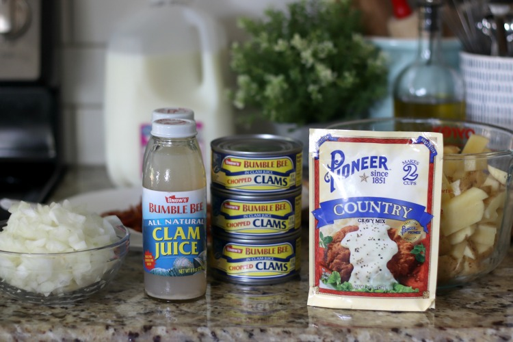bowl of onions with two bottles of clam juice and 3 cans of clams next to a packet of country gravy mix and bowl of diced potatoes