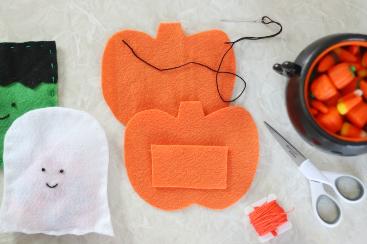 two felt pumpkins next to scissors and string