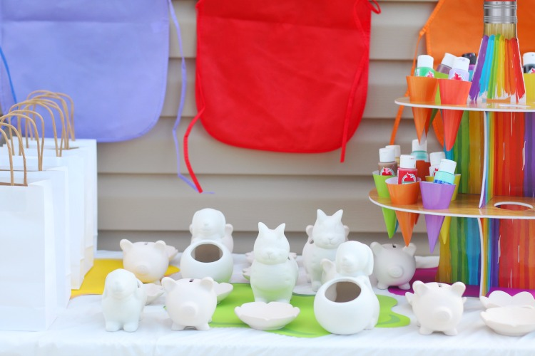 unpainted pottery on table next to white gift bags