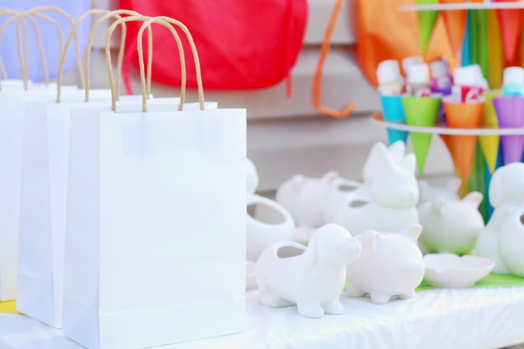 white gift bags to put finished pottery in next to unpainted pottery