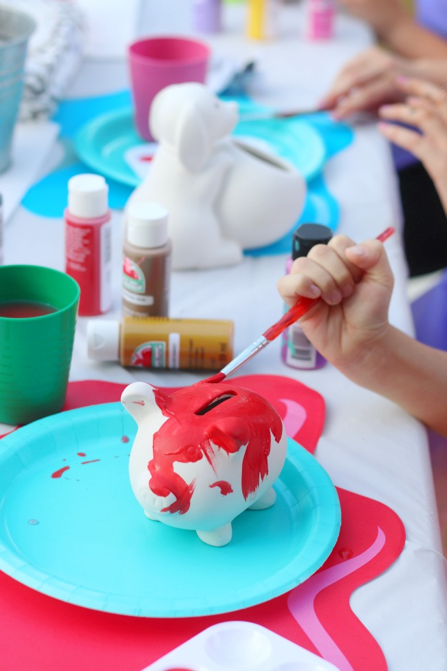 little boy painting a red piggy bank
