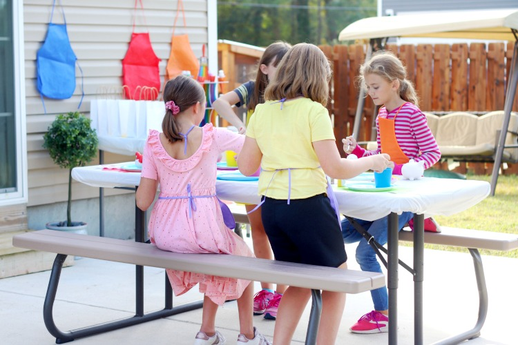 kids sitting at table painting together