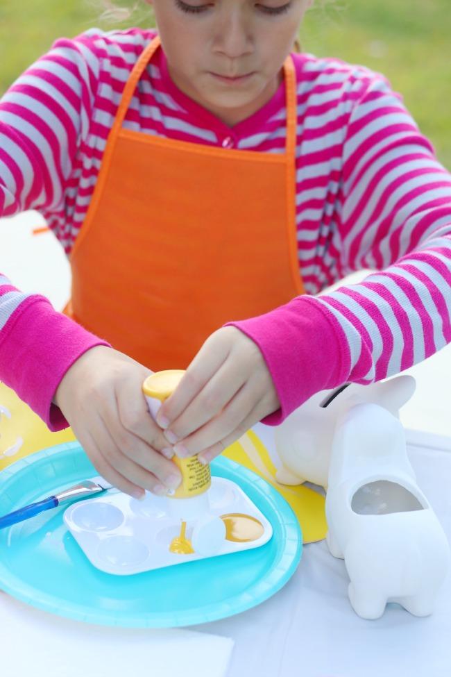 child pouring paint onto paint palette