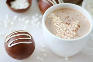 hot chocolate bomb next to white mug of hot chocolate