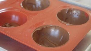 silicone chocolate mold with chocolate spooned inside