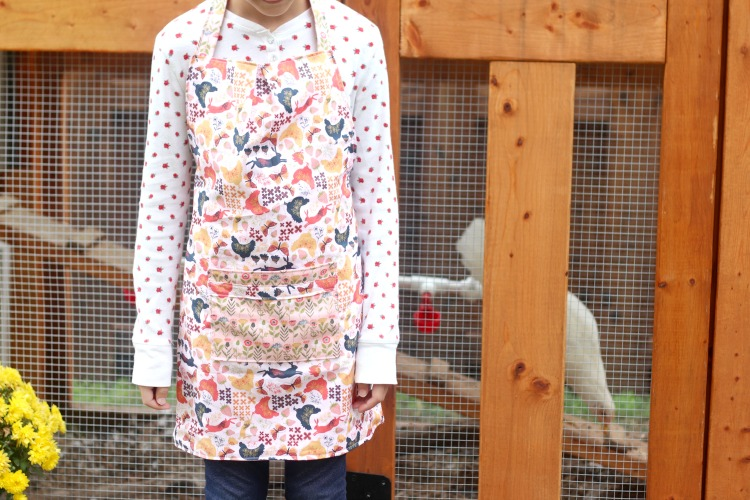 child standing in apron by chicken coop