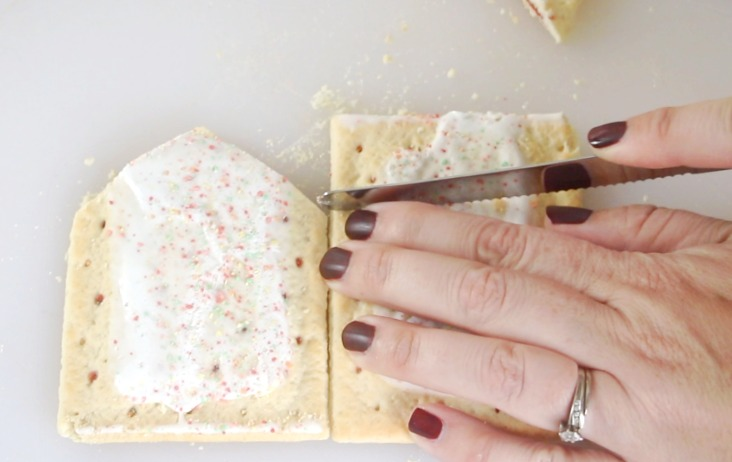 hand holding serrated knife to cut pop tarts
