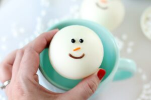 hand holding snowman hot chocolate bombs over mug