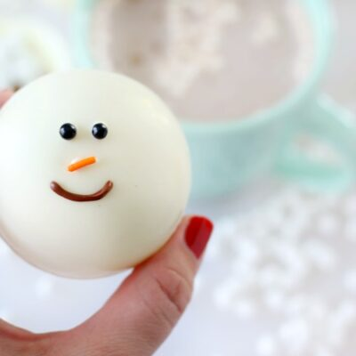 hand holding snowman hot chocolate bomb