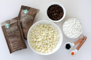 bowl of white chocolate chips next to bowls of chocolate chips and mini marshmallows and cocoa mix
