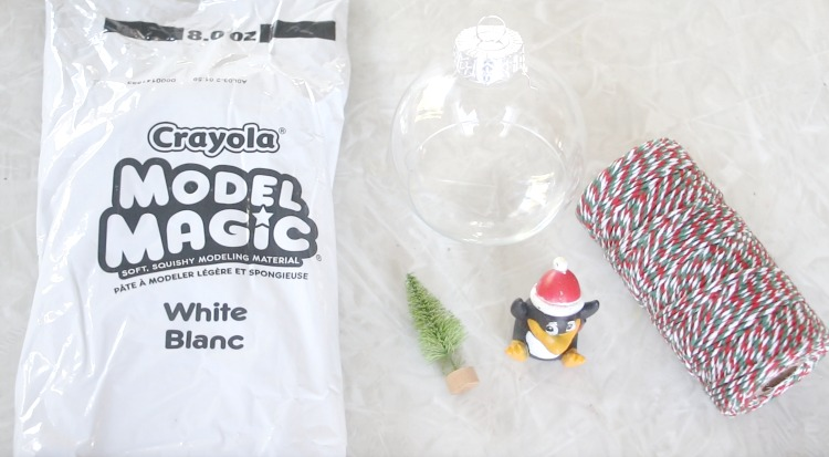white model magic next to penguin finger puppet and clear ornament