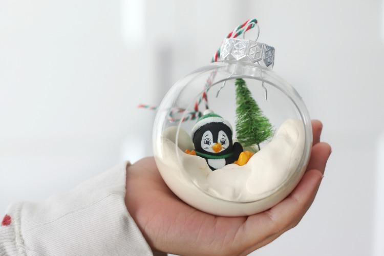 child holding penguin ornament