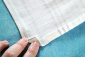 corner on fabric folded over for hem on cloth napkin