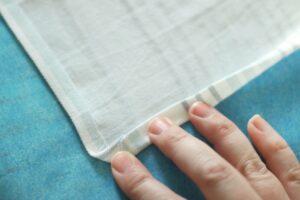 edge of fabric folded over for hem on cloth napkin