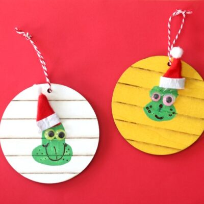 two thumbprint grinch ornaments on red background