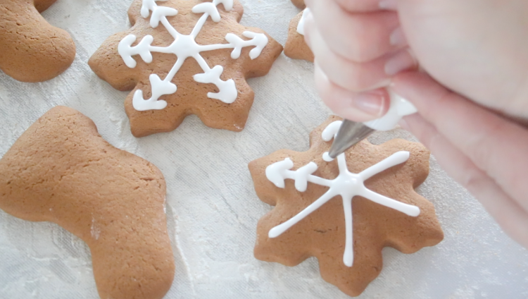 hand piping icing on quick gingerbread cookies
