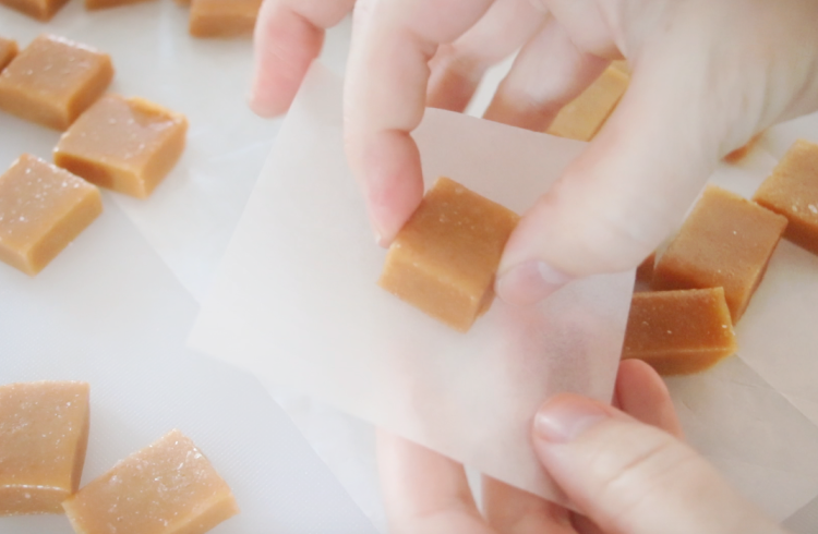 hands wrapping piece of microwave caramel in parchment paper