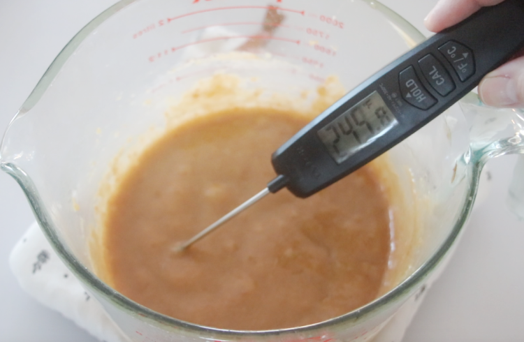 candy thermometer dipped into hot caramel mixture