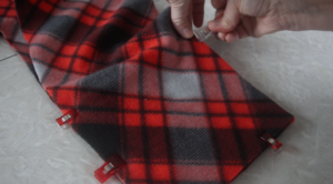 hand placing sewing clips around fleece scarf