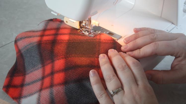 hands feeding fleece fabric through sewing machine