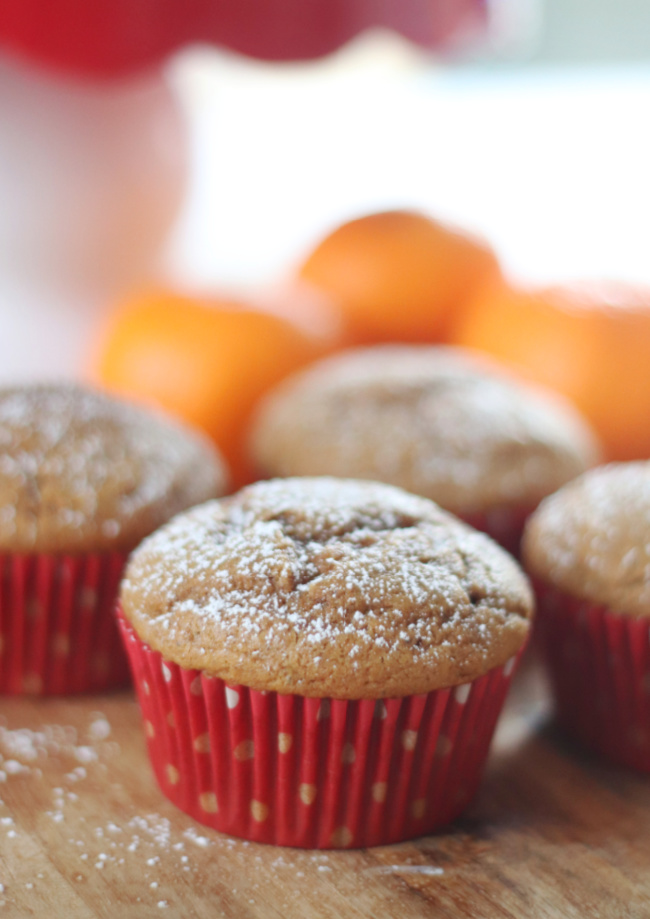 gingerbread muffins on cutting board with oranges in background