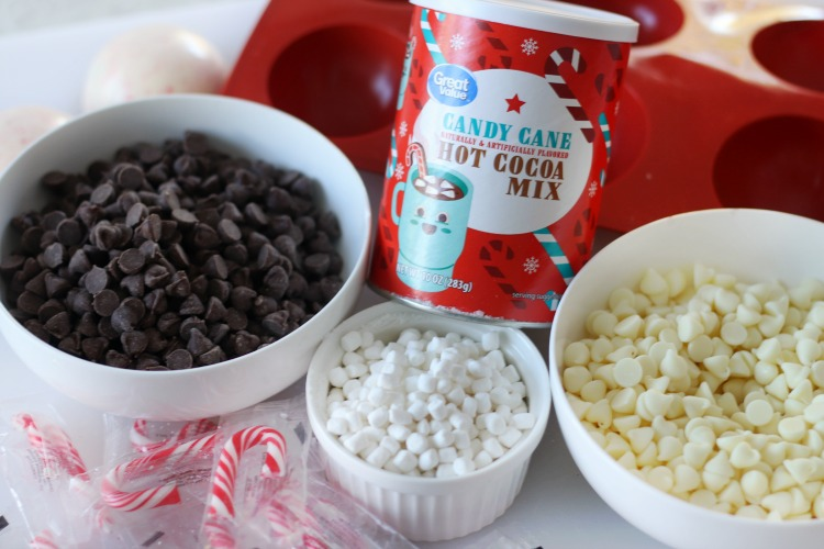 chocolate chips, white chocolate chips, peppermint hot cocoa mix, candy canes and marshmallows in bowls