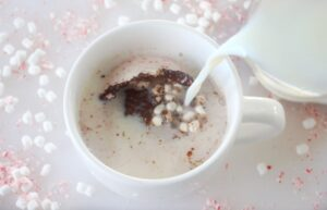 hot milk being poured over hot chocolate bomb