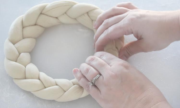 hands bringing ends of pretzel braid together