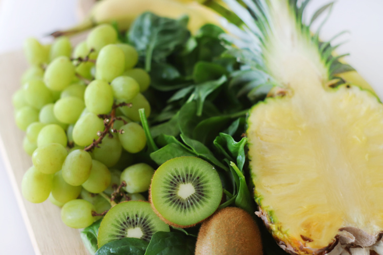grapes, pineapple, spinach, kiwi on cutting board