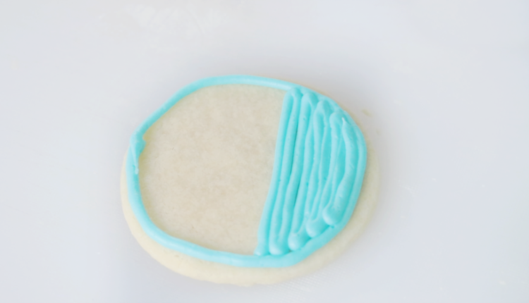 round sugar cookie outlined in blue frosting