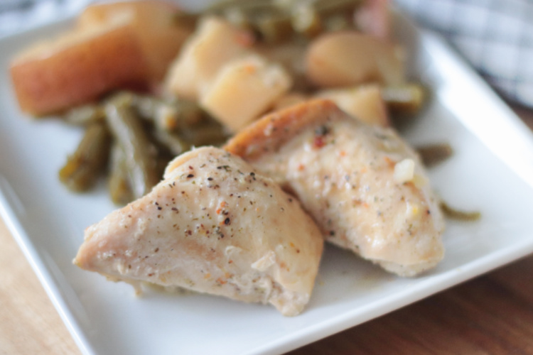 white plate with chicken, potatoes and green beans