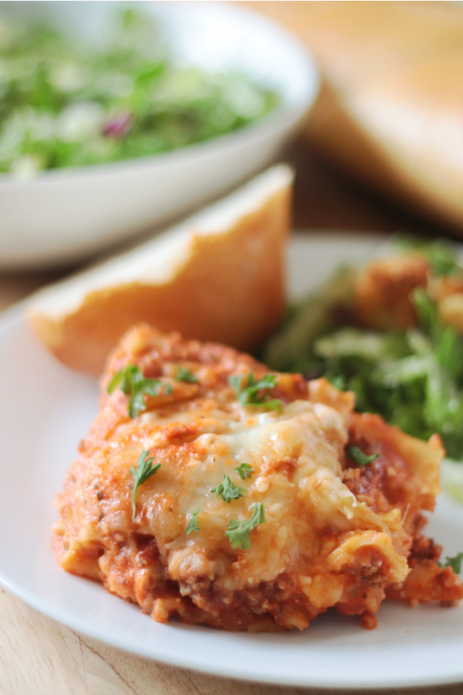 plate with a slice of slow cooker lasagna, salad and bread