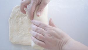 hands rolling up dough