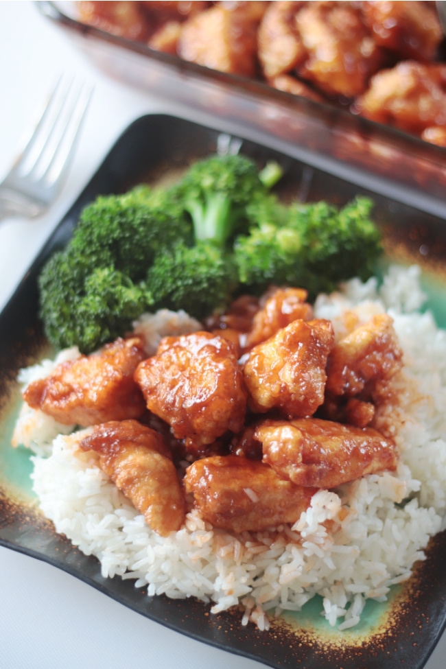 plate of rice broccoli and orange chicken