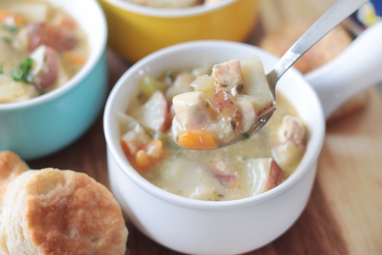 white bowl of slow cooker chicken pot pie soup and spoon