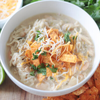 bowl of slow cooker white chicken chili with cheese and chips