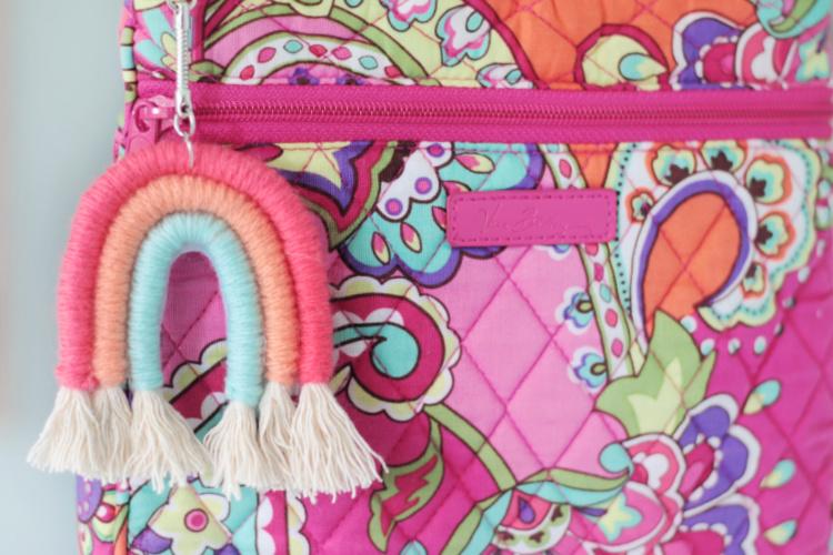 rainbow yarn keychain attached to pink purse