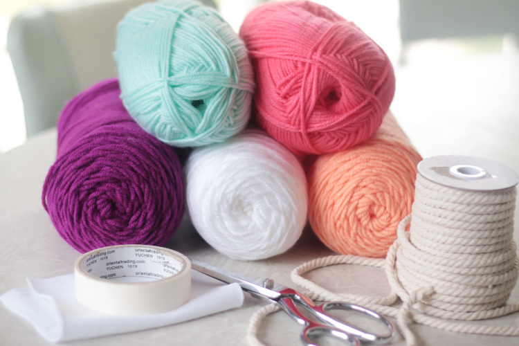 5 skeins of yarn, a spool of rope, scissors, tape and felt